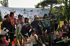 People gathered in front of the banner with their bird drawings
