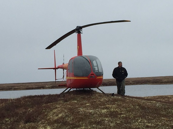 Robinson R44 helicopter and pilot Shannon Glenn as he waits for us to return from a shorebird survey © Richard Lanctot